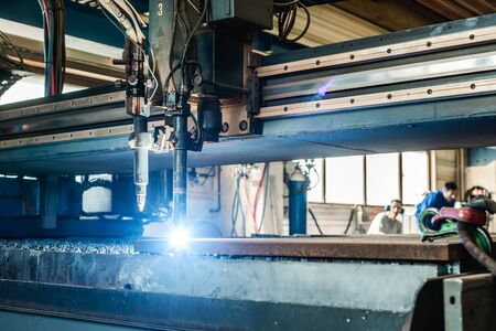 Plasma cutter in a factory cutting thick piece of metal