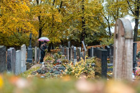 Graves on cemetery in autumn with a couple mourning the dead standing between the graves