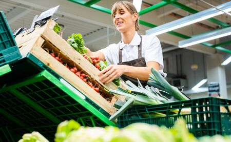 Woman working in a supermarket sorting fresh fruit and vegetables Stock Photo