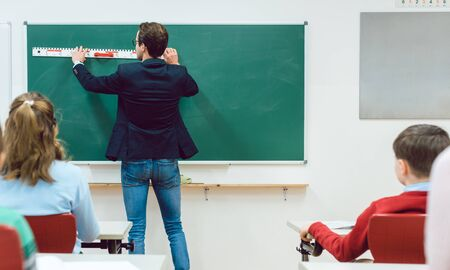 Attentive students watching teacher drawing at the blackboard in classroom
