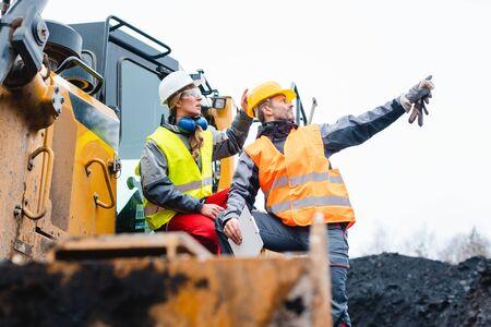 Mann und Frau als Arbeiter am Bagger im Steinbruch, die auf Dinge zeigen Standard-Bild