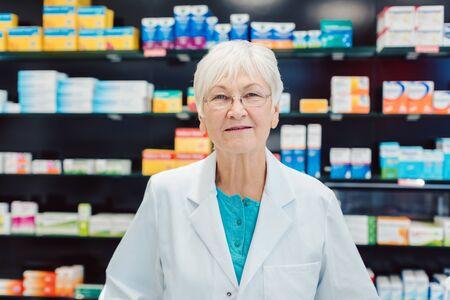 Farmacéuticos senior experimentados delante de los estantes de la farmacia mirando a la cámara