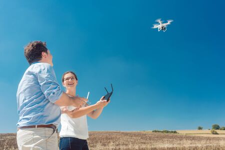 Crew or man and woman operating a drone to utilize it for a photo or film shoot