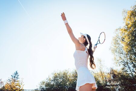 Woman serving the ball in tennis match on the court 写真素材