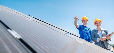 Gerente y trabajador en planta de energía fotovoltaica discutiendo el mantenimiento de la granja solar