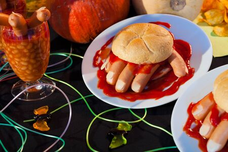 Hot dog in shape of human hand kept in burger with sausage as blood for halloween