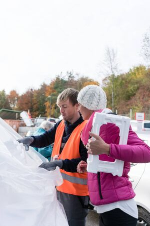 Woman and man on recycling center with Styrofoam in hands