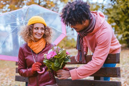 Man surprising his wife with a bouquet of flowers on a drizzly fall day to bring joy to her life