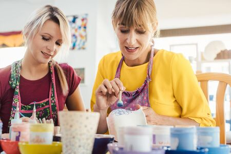 Women in DIY workshop coloring and decorating their own ceramic dishes
