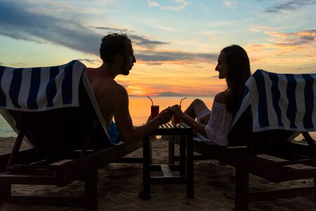 Rear view of a young romantic couple in love, sitting on wooden chairs while drinking cocktails on a tropical beach at sunset during vacation or honeymoon in Indonesia