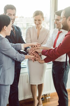 Diversity team of business people in kick-off meeting stacking hands together