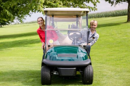 Portrait of happy young couple sitting in the golf cart peeking
