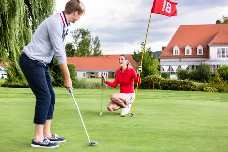 Smiling girlfriend holding flag looking at male golfer putting the golf ball in green Archivio Fotografico