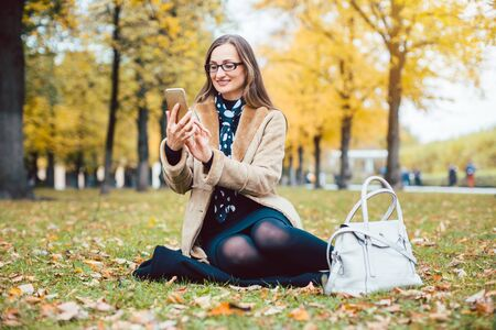 Woman texting with the phone sitting on an autumn lawn in a park 스톡 콘텐츠