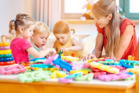 Group of children and teacher playing practical games in kindergarten Standard-Bild