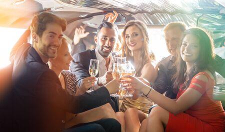 Gruppe von Frauen und Männern, die in einer Limousine mit den Gläsern anstoßen, Spaß haben und glücklich sind