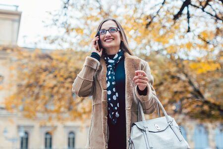 Beautiful woman using her phone standing in the city in autumn
