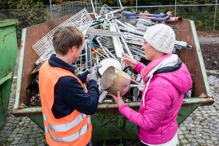 Mujer poniendo una gran cantidad de chatarra en un contenedor para ser reciclada