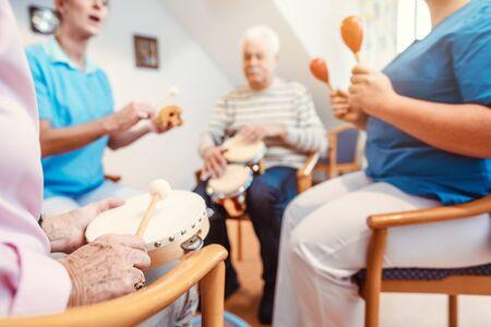Senioren im Pflegeheim Musizieren mit Rhythmusinstrumenten als Musiktherapie Standard-Bild