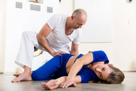 Male instructor helping female student with correct pose