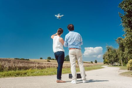 Crew or man and woman operating a drone to utilize it for a photo or film shoot Stock fotó