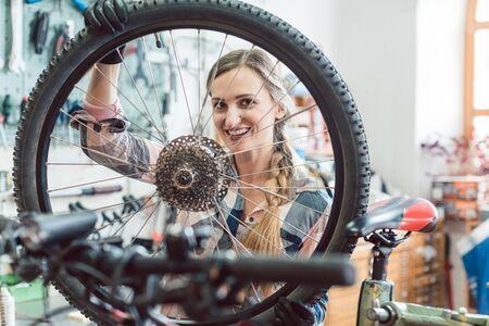 Very happy bike mechanic woman looking through the wheel of bicycle