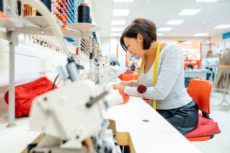Absorbed seamstress working in her studio sewing clothes Stock Photo