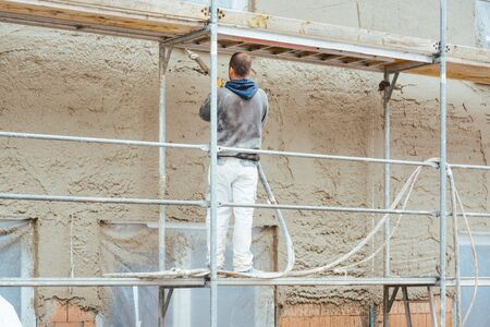 Construction worker plastering outer wall of newly built house