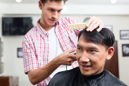 Barber making haircut of an attractive man in barbershop