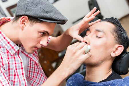 Young male barber wearing baseball cap shaving with razor