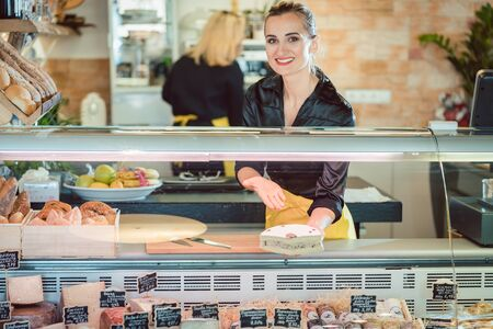 Friendly women selling cheese at counter in a supermarket Archivio Fotografico - 131709329