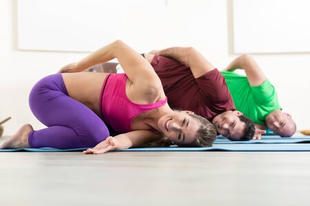 People doing yoga together in fitness studio 스톡 콘텐츠