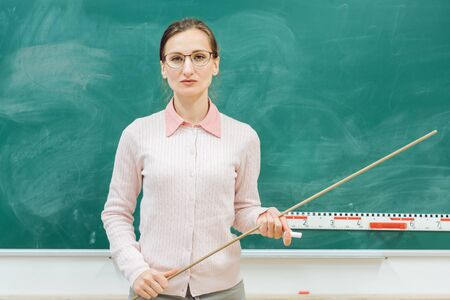 strict teacher standing in front of blackboard in class with a pointer in hand