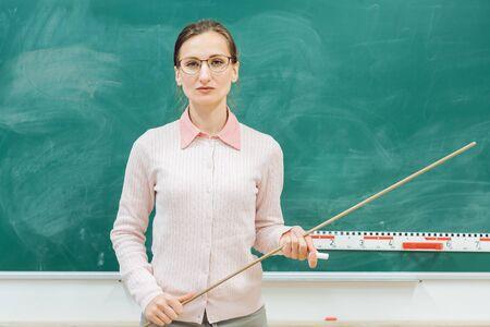 Strenger Lehrer, der in der Klasse mit einem Zeiger in der Hand vor der Tafel steht Standard-Bild
