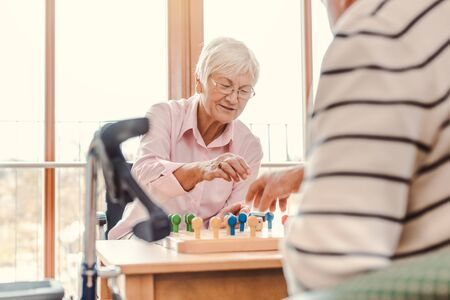 Two seniors, man and woman, in a nursing home playing a board game Standard-Bild - 131709482
