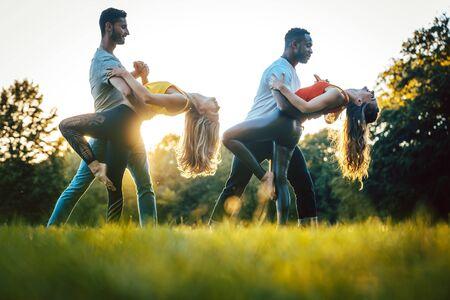 Women and men performing dance moves against backlit park
