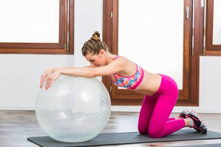 Side view of woman doing exercise on pilates ball on exercise mat in gym Banco de Imagens