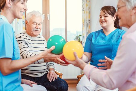 Group of seniors doing sport and gymnastics with balls in the pensioners home Standard-Bild - 130846714