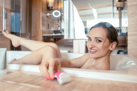 Woman having bath in hotel bathtub grabbing shaver for hair removal on her legs
