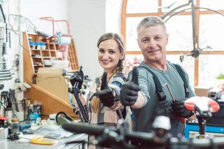 Two bike mechanics in their workshop having a successful day showing their thumbs