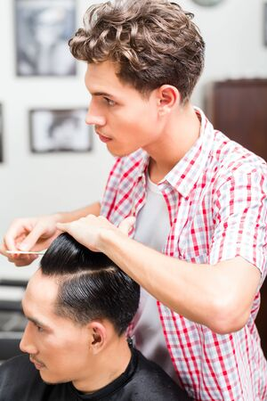 Professional young male hairdresser hairstyling the clients hair