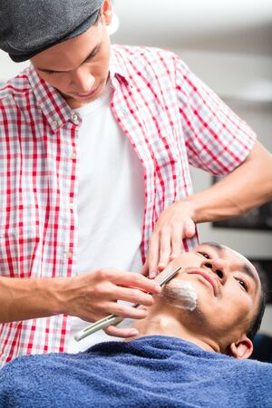Close-up of hairdresser shaving with straight razor in salon
