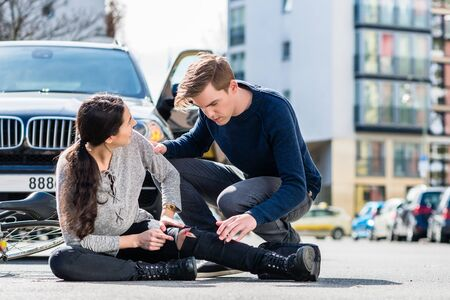 Young male driver using a sterile adhesive bandage from his first aid kit to help an injured female bicyclist on the street Stockfoto