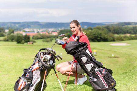 Portrait of smiling female player crouching choosing golf club from bag