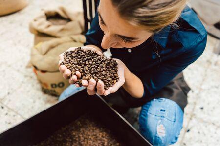 Femme barista testant l'arôme des grains de café frais reniflant