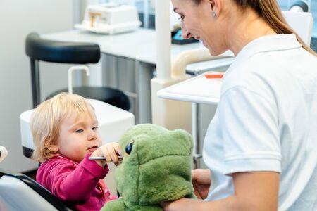 Niño en la cirugía de dentistas aprendiendo a cepillarse los dientes con un cepillo de dientes gigante