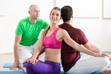 Close-up of male instructor correcting yoga pose in fitness studio