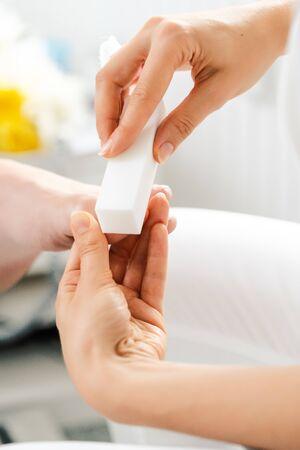 Woman podiatrist polishing nail of man during pedicure with file Stock fotó