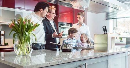 Expert explaining new kitchen to family looking for one pointing at some interesting features of the current model