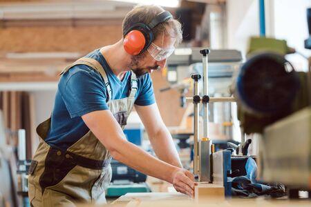 Geabsorbeerde timmerman met gehoorbescherming en veiligheidsbril bij de freesmachine die op hout werkt